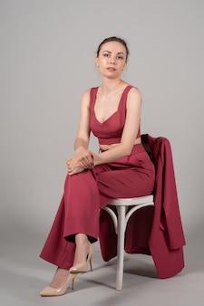 魅力的なシックなビジネス女性の完全な長さの写真は、赤いスーツのハイヒールの孤立した灰色の背景を着て椅子に座る