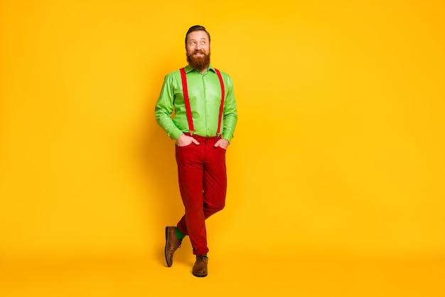 Полная длина фото привлекательного фанк-парня с хорошим настроением, смотрящего в сторону пустого пространства, веселая одежда, зеленая рубашка, красные подтяжки, брюки, носки, обувь, изолированные желтого цвета
