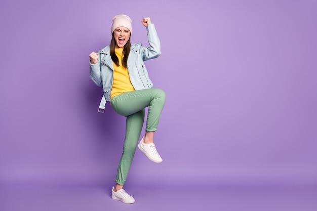 Полная длина фото привлекательной смешной сумасшедшей леди, хорошее настроение, поднять ноги, руки, кулаки, изумленные, выиграть в лотерею, носить повседневную шляпу, современную куртку, брюки, обувь, изолировать фиолетовый цвет фона
