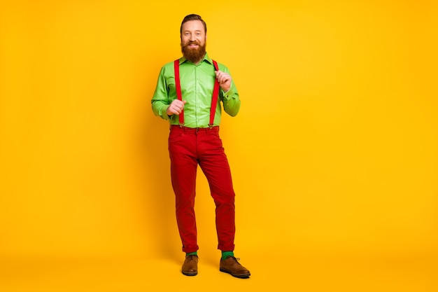 Полная длина фото привлекательного забавного парня с хорошим настроением, веселой зубастой улыбкой, в зеленой рубашке, красных подтяжках, штанах, носках, изолированной обуви, ярких цветов