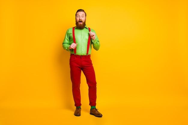 Полная длина фото привлекательного забавного парня модели хорошее настроение взволнованные новости открытый рот носить зеленую рубашку красные подтяжки брюки носки обувь изолированный яркий цвет