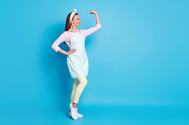 강한 근육 팔을 보여주는 매력적인 아가씨 자신감 집 아내의 전체 길이 사진