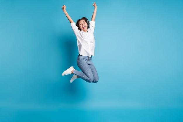 Полная длина фото привлекательной леди, прыгающей в высоком хорошем настроении, носит белую рубашку, джинсовую обувь, изолированный синий цвет фона