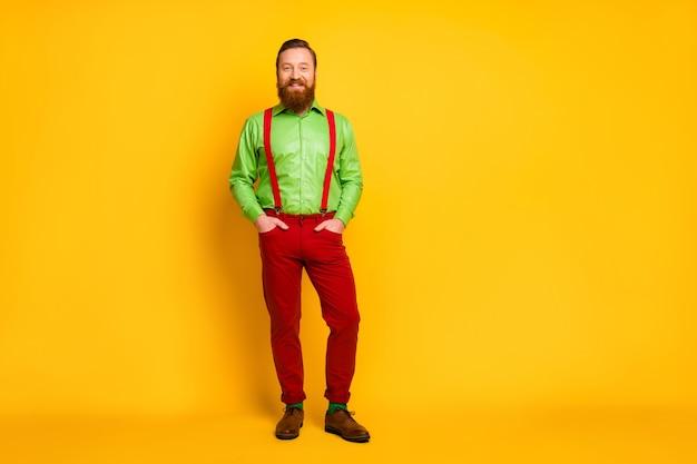 Фото в полный рост привлекательного мачо, забавного парня, хорошего настроения, веселого, зубастого, улыбающегося, в зеленой рубашке, красных подтяжек, брюк, носков, обуви, изолированного цвета блеска