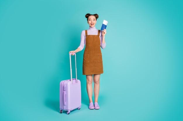 매력적인 꽤 귀엽고 흥분된 탑 매듭 헤어스타일 여성의 전체 길이 사진은 비자 준비가 된 해외 여행 가방을 들고 보라색 스웨터 신발 갈색 드레스 격리된 청록색 배경