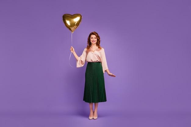 Полная длина фото привлекательной красивой девушки держит воздушный шар в форме сердца