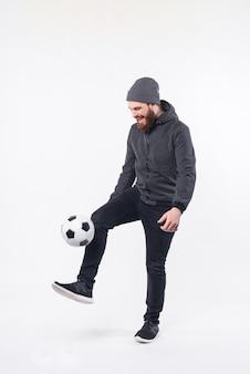 Полное фото бородатого хипстера, играющего с футбольным мячом