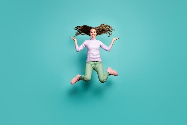 아름 다운 미친 여자 점프 높은 긴 곱슬 머리 공기 기쁨 착용 보라색 점퍼 녹색 바지 신발 절연 블루 청록색 파스텔 색상의 전체 길이 사진