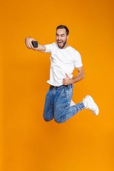 カジュアルな服装で笑って携帯電話で自分撮りをしている30代の美しい男の全身写真、分離