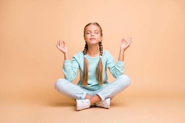 Фотография в полный рост красивой маленькой леди, сидящей на полу, скрещенными глазами, закрытыми пальцами вместе, поза лотоса, медитации, одежда, синий свитер, джинсовая обувь, изолированные на стене бежевого цвета