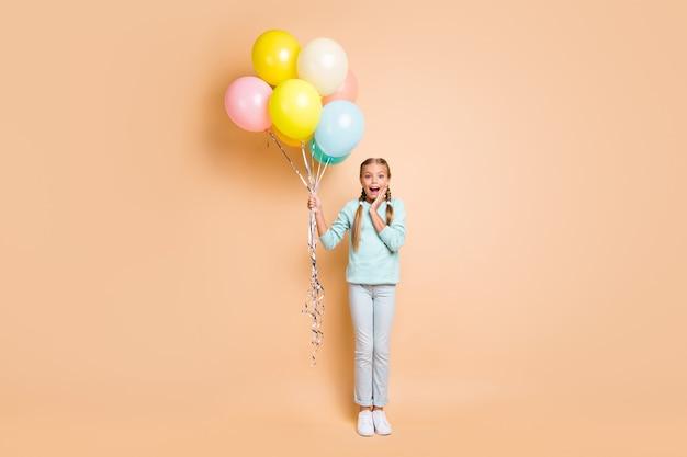 Полная длина фото красивой маленькой леди, много разноцветных воздушных шаров, сюрприз, праздничный день рождения, рука на щеке, синий свитер, джинсы, кроссовки, изолированные на бежевой стене в пастельных тонах