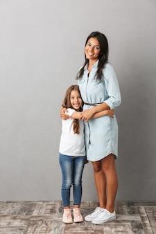 小さな女の子が笑顔で抱き合って、灰色の上に分離された美しい女性の全身写真