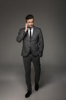 灰色の壁に分離された携帯電話で話しながらネクタイとフォーマルスーツに身を包んだ30代のビジネスマンの完全な長さの写真