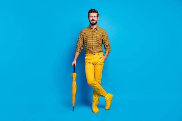 Полная фотография откровенного импозантного мужчины, отдыхающего, расслабляющегося, яркого защитного щита, зонтика от дождя, одежды, современной одежды, обуви, изолированной на синем цвете