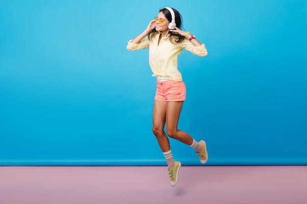 スニーカーで踊るのんきなスポーティな白人の女の子のフルレングスの写真。幸せな感情を表現し、ジャンプするヘッドフォンでうれしいブルネットのアジアの女性モデル。