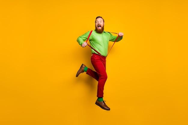 Полная длина фото беззаботного детского сумасшедшего фанк-человека в прыжке, тянущего его современные подтяжки, кричащего, радуйтесь, наденьте стильную спортивную обувь, изолированную желтым цветом