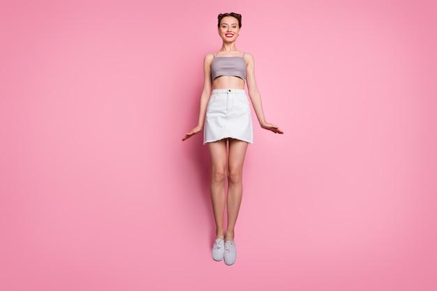 매력적인 귀여운 소녀 점프의 전체 길이 사진은 봄 자유 시간이 핑크 색상 위에 고립 된 재미있는 착용 캐주얼 스타일의 옷을 즐길 수 있습니다