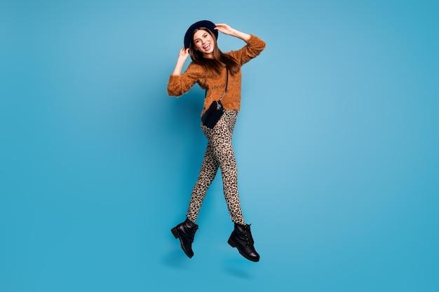 Фотография в полный рост очаровательной милой девушки в прыжке, прикоснитесь к ее шляпе в стиле ретро, наслаждайтесь эмоциями, носите повседневную одежду, клатч, черные сапоги, изолированные на стене синего цвета