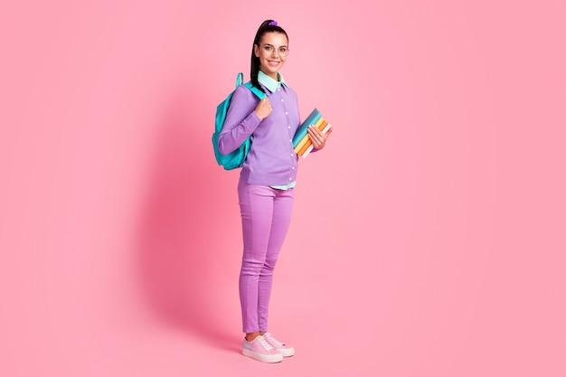 Полная длина фото очаровательной девушки держать кучу книжной одежды спецификации рюкзака фиолетовый пуловер брюки кроссовки изолированный розовый цвет фона
