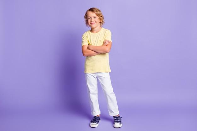 Полная длина фото очаровательного мальчика с перекрещенными руками в стильной одежде, изолированной на фиолетовом цветном фоне