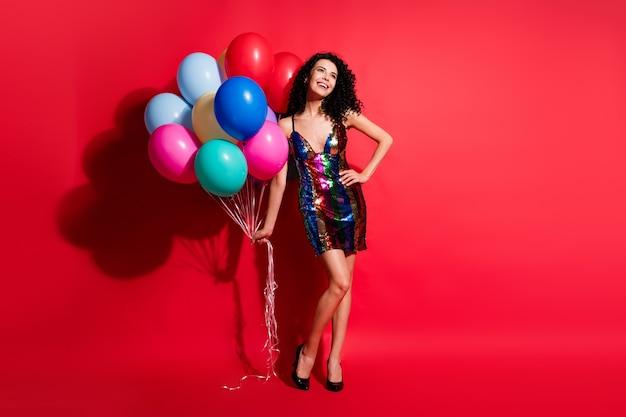 Полная длина фото очаровательной дамы с воздушными шарами выглядит пустым пространством в глянцевом мини-платье на высоких каблуках, изолированных на ярком красном цветном фоне