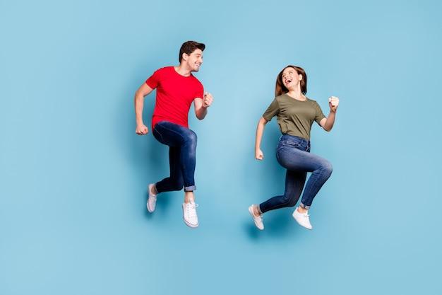 매력적인 배우자의 전체 길이 사진 휴식 점프 실행 파란색 배경 위에 절연 녹색 빨간색 티셔츠 데님 청바지 운동화를 착용 휴식