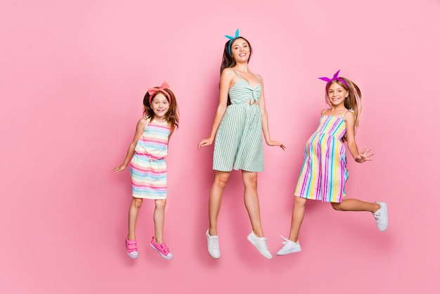 Полная длина фото очаровательных трех человек, прыгающих в платье с повязкой на голову, изолированном на розовом фоне