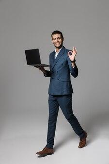Полная длина фото веселого арабского бизнесмена 30-х годов в официальном костюме, улыбающегося и держащего ноутбук, изолированного над серой стеной