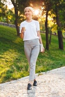 テイクアウトコーヒーと緑の都市公園を散歩しながら、笑顔でカジュアルな服を着ている陽気な金髪の女性の全身写真