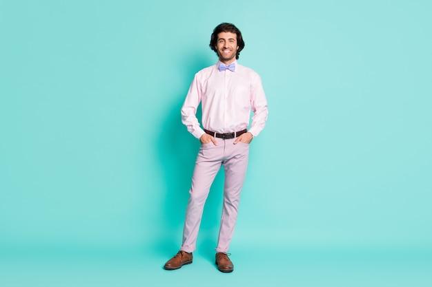 Полная длина фото веселого щетинного джентльмена, одетого в розовый наряд, руки, карманы, изолированного бирюзового цвета