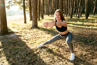Full length photo of cheerful fit girl in sportswear doing stretching sport exercises