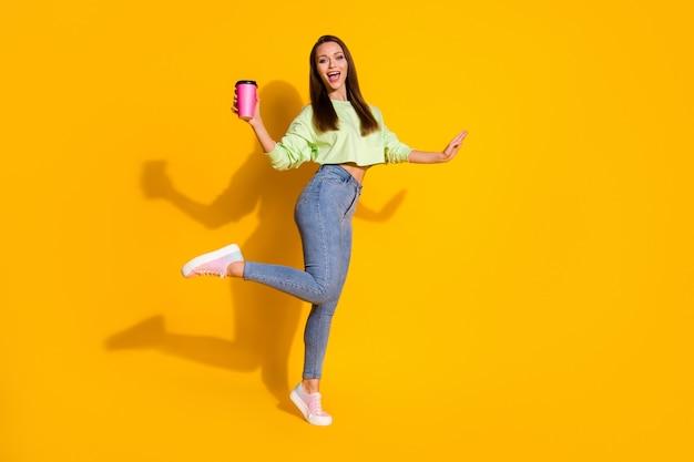 Полная фотография веселой смешной девушки наслаждается выходными, держа кружку с напитком на вынос