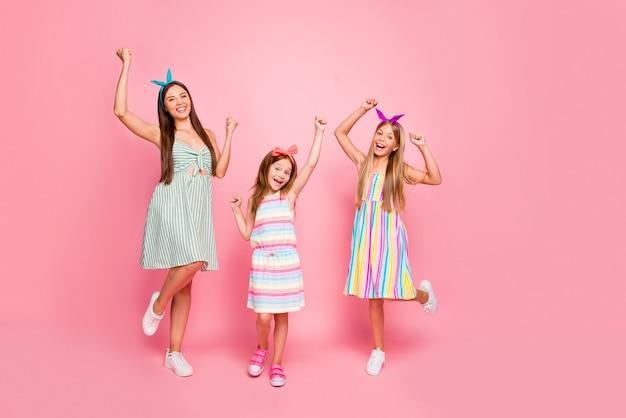 ヘッドバンドで長い散髪をしている陽気な女の子の全身写真は、ピンクの背景の上に分離された勝利を祝うスカートドレスを着用して拳を叫びます