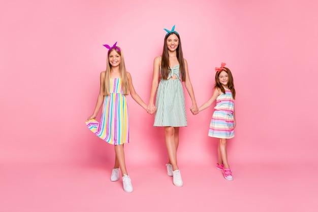ピンクの背景で隔離のドレススカートを着て手をつないで明るいヘッドバンドを持つ陽気な女の子の完全な長さの写真