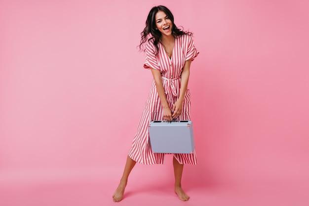 スーツケースを手に踊る陽気な女性の全身写真。裸足でポーズをとるミディ丈の衣装でカールした日焼けしたブルネット。