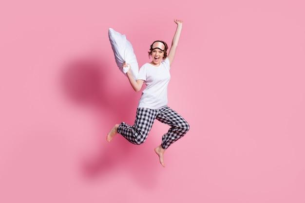 元気な女性の全身写真が枕投げの高さまでジャンプ