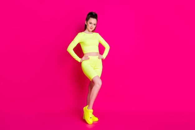 Полная длина фото веселой прекрасной молодой женщины, одетой в желтую спортивную одежду, руки, талию, изолированного розового цвета фона