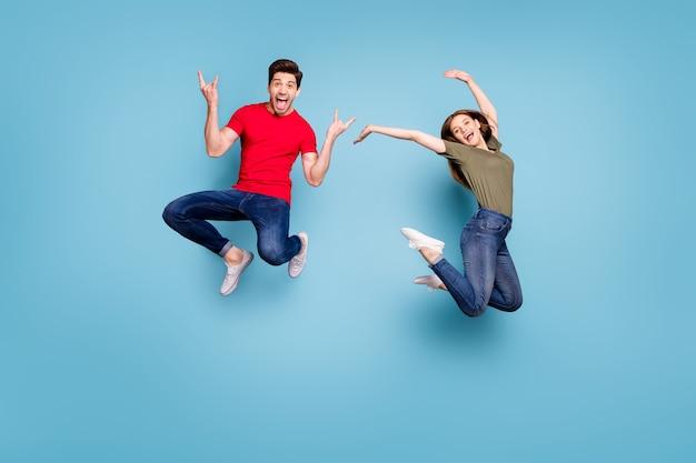 쾌활한 두 사람이 학생 남자 중금속 연인 쇼 뿔 여자 점프 인상 손의 전체 길이 사진은 녹색 빨간색 티셔츠 데님 청바지 절연 파란색 배경을 착용