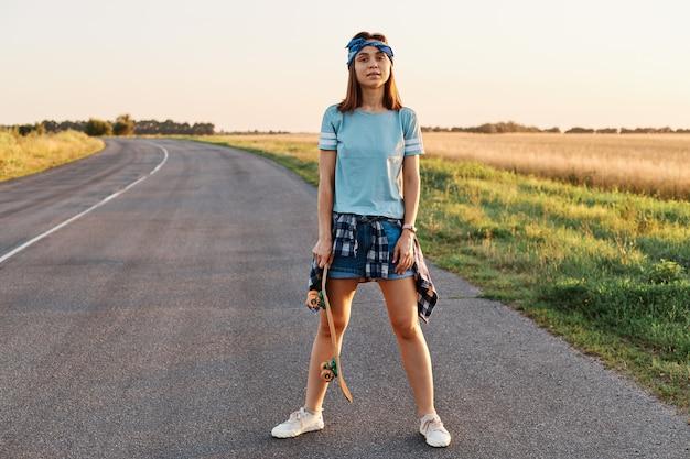 屋外でスケートボードをした後、ショート、tシャツ、ヘアバンド、手にスケートボードを持って、カメラを見て、自信を持って満足している女性の全身写真。