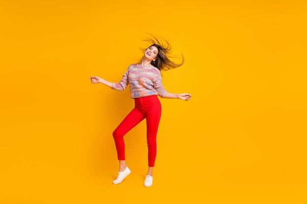 Полная длина фото содержания прекрасная милая игривая девушка наслаждается праздничными выходными, ее прическа летать ветер ветер носить обувь джемпер, изолированные на ярком цвет