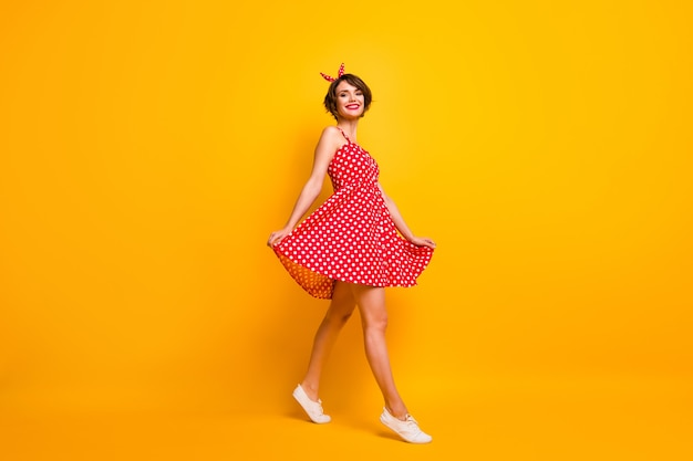 Полная фотография довольной милой девушки, которая наслаждается весенними выходными, иди, гуляй, прикоснись к ее юбке в винтажном стиле, надень белые кроссовки, изолированные на яркой цветной стене