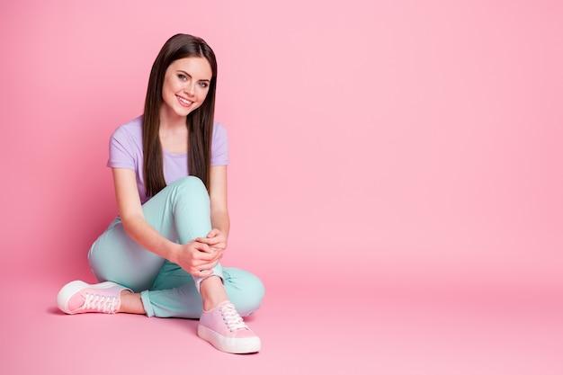 Полная длина фото контента, симпатичная девушка сидит на полу, наслаждайтесь отдыхом на выходных, расслабьтесь, носите красивую одежду, изолированную на розовом цветном фоне