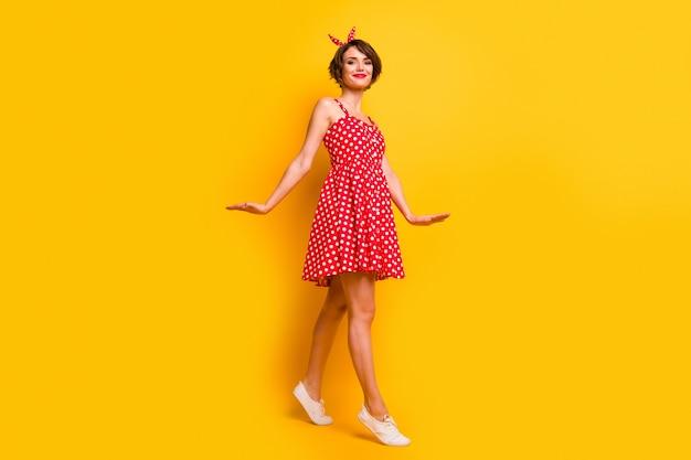 Полная фотография довольной красивой девушки, которая наслаждается весенними выходными в свободное время, гуляет в одежде в горошек, изолированной над яркой цветной стеной