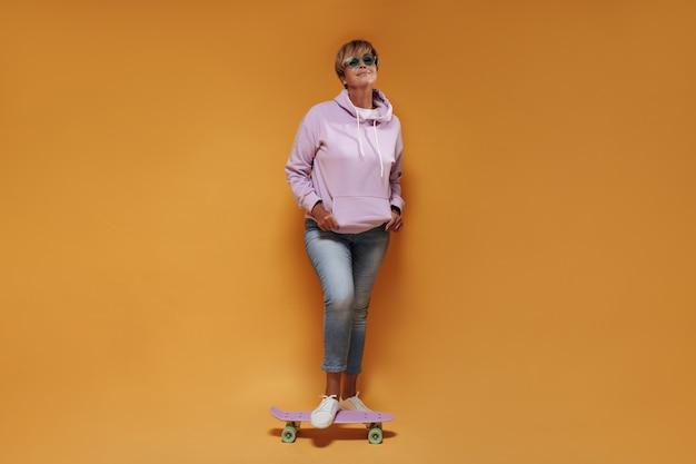 サングラス、ワイドパーカー、スキニージーンズの短い髪のクールな女性のフルレングスの写真は、ピンクのスケートボードで笑顔とポーズをとっています。