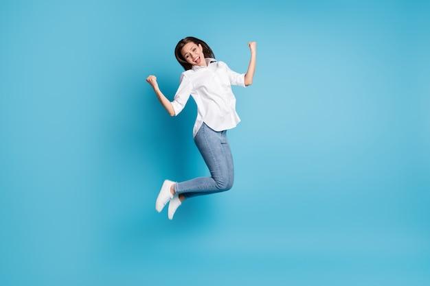 Полная длина фото сумасшедшей леди, прыгающей высоко, радуясь, поднимая кулаки, в белой рубашке, джинсовой обуви, изолированной на синем фоне