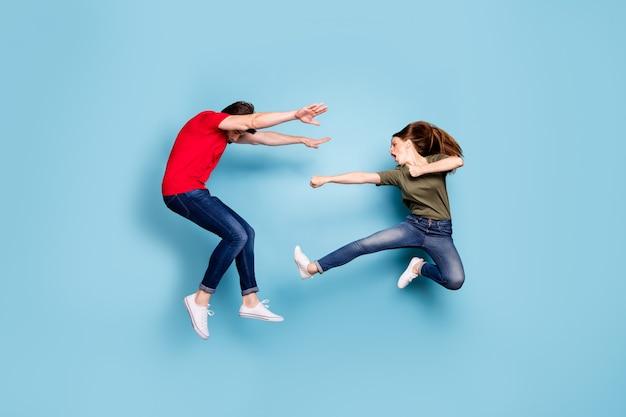 미친 미친 두 사람의 배우자 여자의 전체 길이 사진 동의 점프 싸움 킥 남자 가을 착용 녹색 빨간색 티셔츠 데님 청바지 스니커즈 파란색 배경 위에 절연