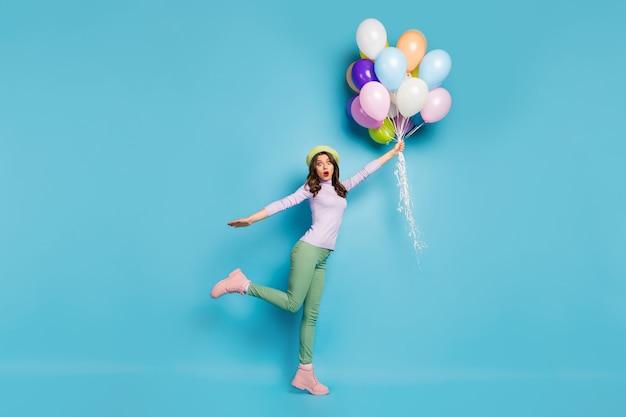 미친 예쁜 아가씨의 전체 길이 사진은 많은 공기 풍선을 들고 바람이 입고 보라색 풀오버 베레모 모자 녹색 바지 부츠 격리 된 파란색 벽으로 제기 충격