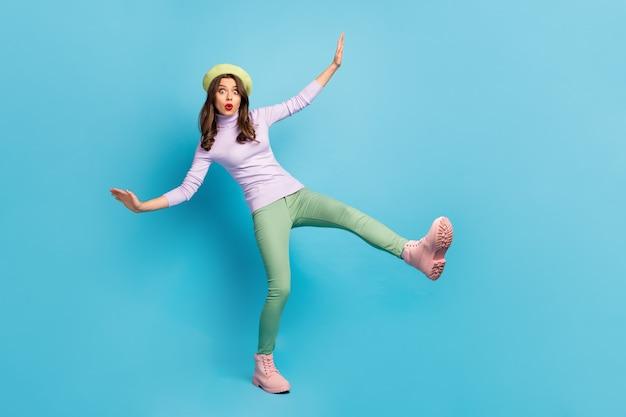 Полная фотография сумасшедшей напуганной туристки, идущей по скользкой улице, падающие глаза, полная страха, носить зеленый берет, фиолетовые джемперские брюки, туфли, изолированные на стене синего цвета