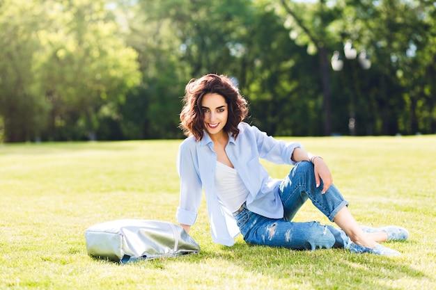 공원에서 햇빛에 잔디에 포즈를 취하는 짧은 머리를 가진 귀여운 갈색 머리 소녀의 전신 사진. 그녀는 흰색 티셔츠, 셔츠, 청바지, 신발, 가방을 착용합니다. 그녀는 카메라에 웃고 있습니다.