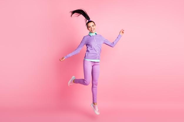 かわいい女の子の完全な長さの写真ジャンプ風ブローヘアウェアバイオレットプルオーバーパンツスニーカー分離ピンク色の背景